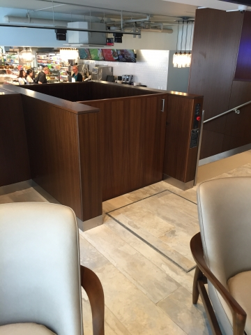 Lift doors closed. View of lift from upper level approach. Lift encased in wood millwork blending in with surrounding aesthetics. Lift function readily available, independently operable.
