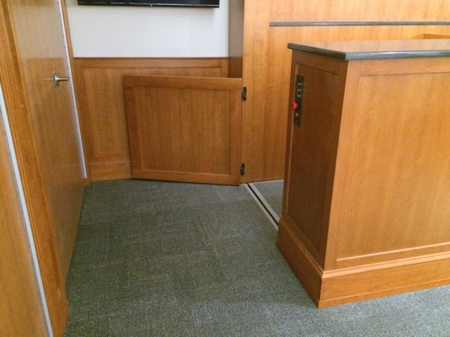 Lift positioned at lower level allowing wheelchair access to the witness stand. The lower level door is opened and the door to the judge bench is closed. Lift encased in wood millwork blending in with courtroom millwork. Lift is readily available and independently operable.