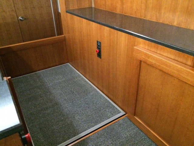 View of the lift from the judge bench. Lift positioned at the judge or upper level with upper level door opened and the lower level door closed. Lift encased in wood millwork blending in with courtroom millwork. Lift is readily available and independently operable.