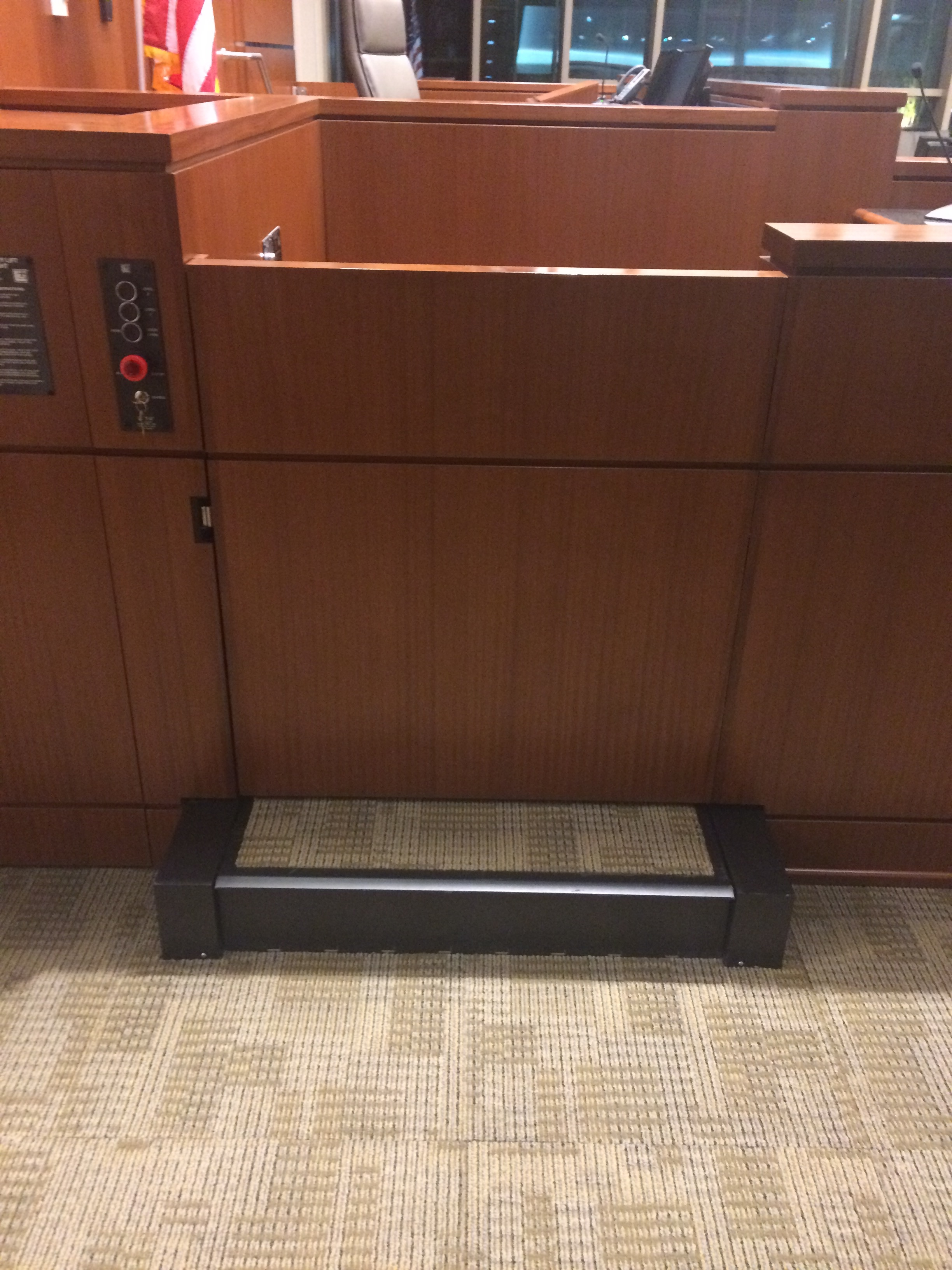 Witness lift positioned at witness level with lower level door closed. Equipped with operable step to allow ambulatory access. Lift encased in wood millwork blending in with courtroom millwork. Lift is readily available and independently operable