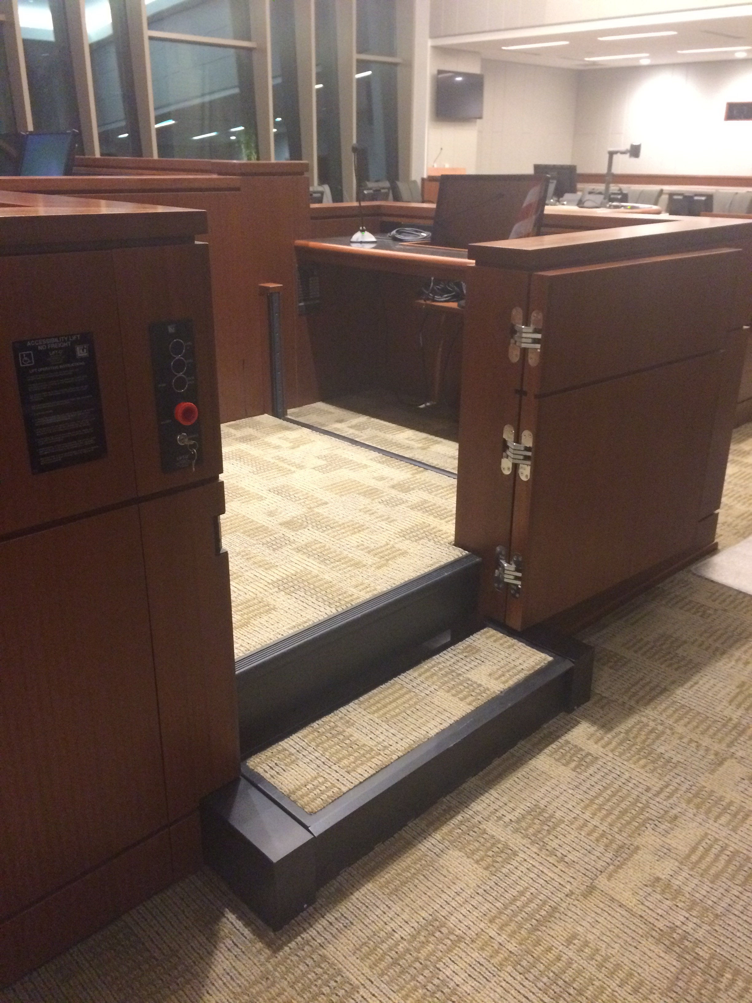 Witness lift positioned at witness level with lower level door opened. Equipped with operable step to allow ambulatory access. Lift encased in wood millwork blending in with courtroom millwork. Lift is readily available and independently operable.