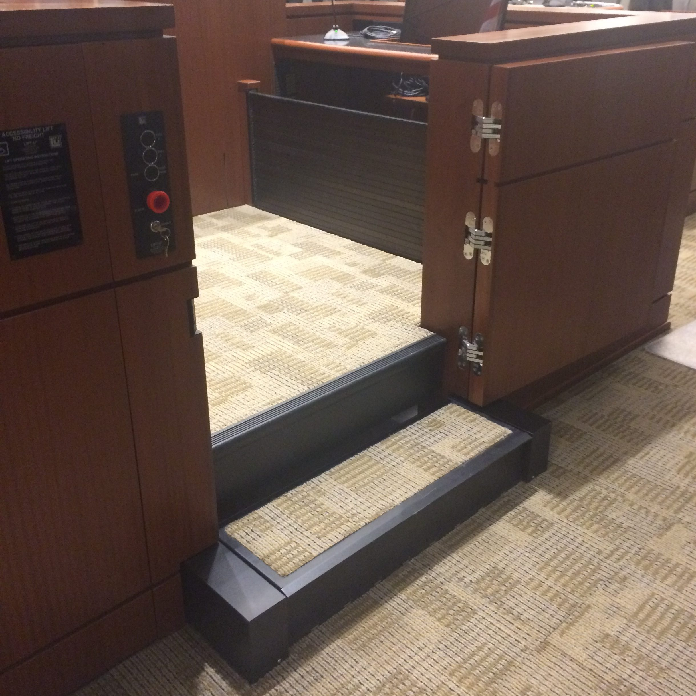 Witness lift positioned at witness level with lower level door opened. Equipped with operable step to allow ambulatory access. Roll-up barrier is up to guard the desk area during lift operation. Lift encased in wood millwork blending in with courtroom millwork. Lift is readily available and independently operable