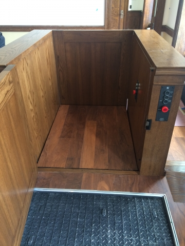 View of the lift from the judge's bench. Lift positioned at the judge's bench or upper level. The upper level door is opened and the lower level door is closed. Lift encased in wood millwork blending in with courtroom millwork. Lift is readily available and independently operable.