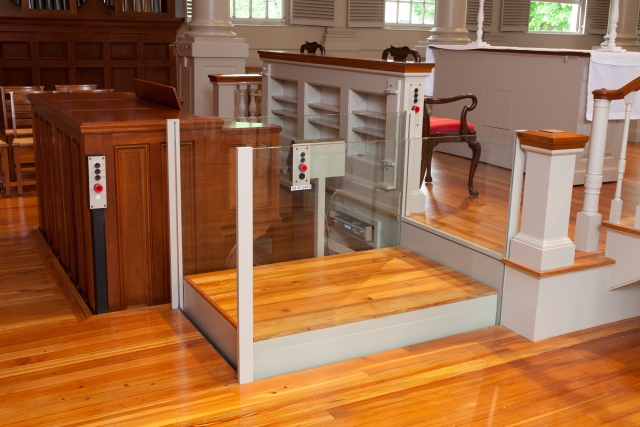 Side view of the lift in a church application with roll-up barriers positioned under the floor allowing ambulatory access to and from the organ. Lift utilizes glass stationary sidewalls to blend in with surrounding aesthetics. Lift function readily available, independently operable.