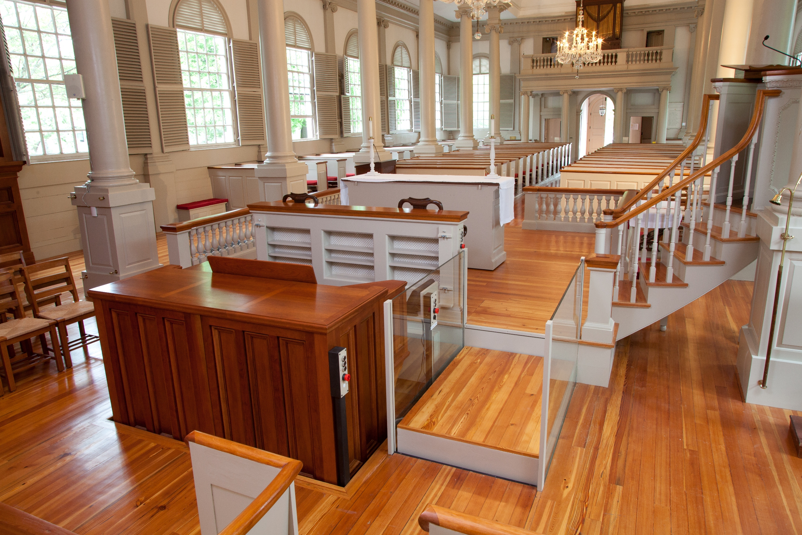 Church application with roll-up barriers positioned under the floor allowing ambulatory access to and from the organ. Lift utilizes glass stationary sidewalls to blending in with surrounding aesthetics. Lift function readily available, independently operable.