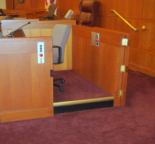 Lift positioned at witness or upper level allowing ambulatory access to the witness stand. The lower level door is opened. Lift encased in wood millwork blending in with courtroom millwork. Lift is readily available and independently operable.