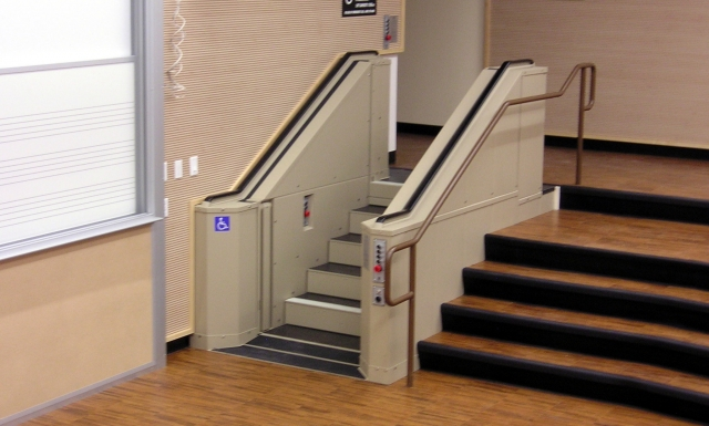 Tan in color. In step position for ambulatory access to lower level of college lecture room. Lift function readily available, independently operable.