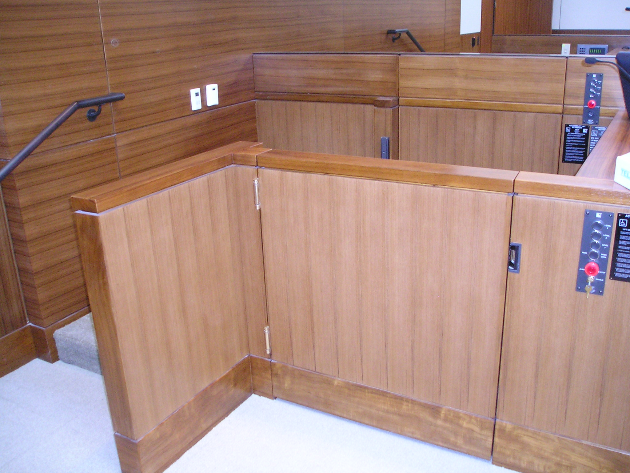 Lift positioned at witness or intermediate level allowing ambulatory access to the witness stand and the judge bench. The lower level door is opened and the door to the judge bench is closed. Lift encased in wood millwork blending in with courtroom millwork. Lift is readily available and independently operable.