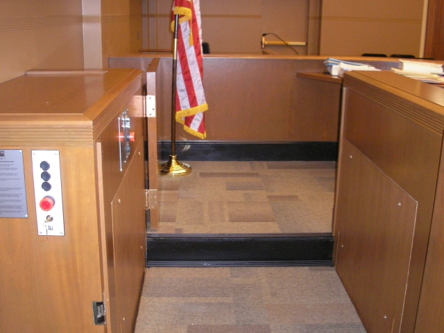 Close-up view of the lift platform at the witness or intermediate level. Both doors are openened allowing ambulatory access to the witness stand and judge's bench. Lift is readily available and independently operable.