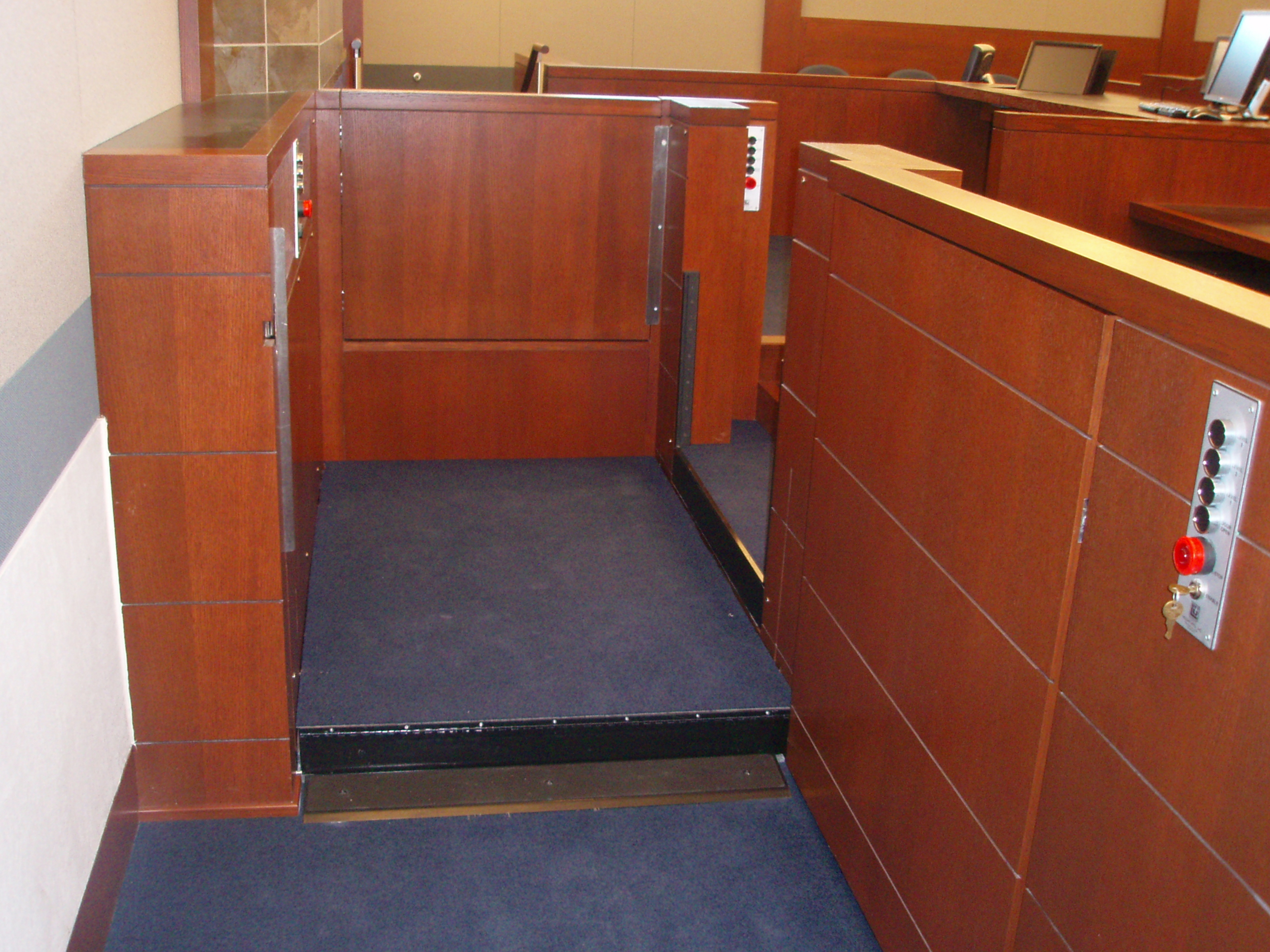 Lift positioned at the second of four levels. The third level is a ninety degree egress to the witness stand. The fourth level is a straight through egress to the judge's bench. Equipped with threshold ramp to allow wheelchair access when the lift is at the lower level. Lift encased in wood millwork blending in with courtroom millwork. Lift is readily available and independently operable.