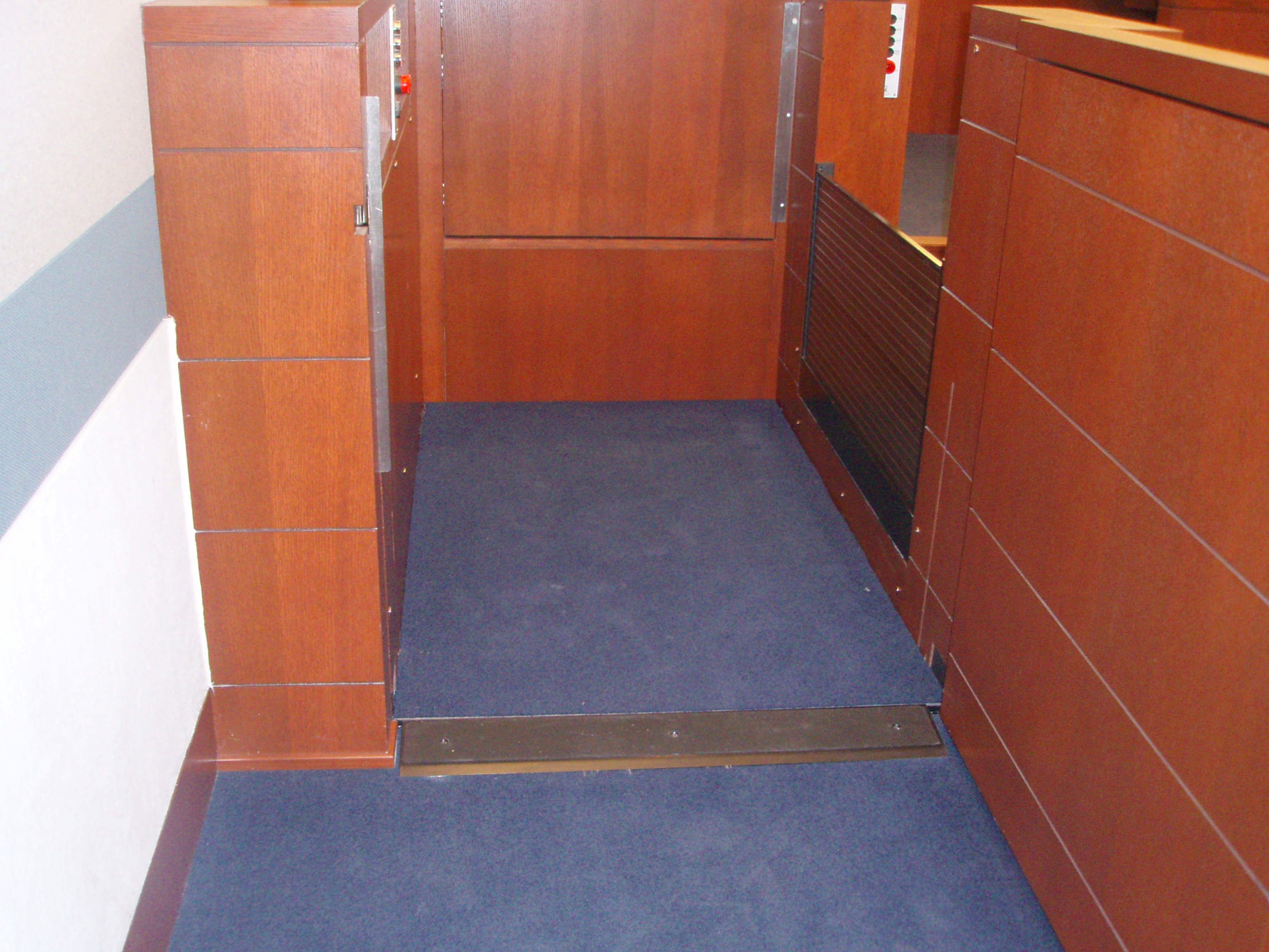 Lift positioned at the lower level. The lower level door is open. Equipped with threshold ramp to allow wheelchair access when the lift is at the lower level. Lift encased in wood millwork blending in with courtroom millwork. Lift is readily available and independently operable.